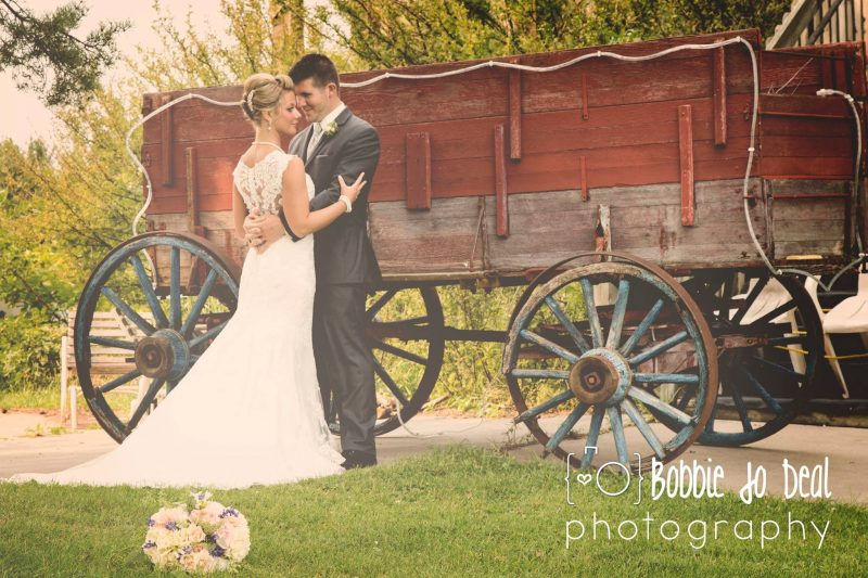 Bride and groom with country wedding wagon at barn wedding venue Country Weddings at Eko Backen in Scandia, Michigan