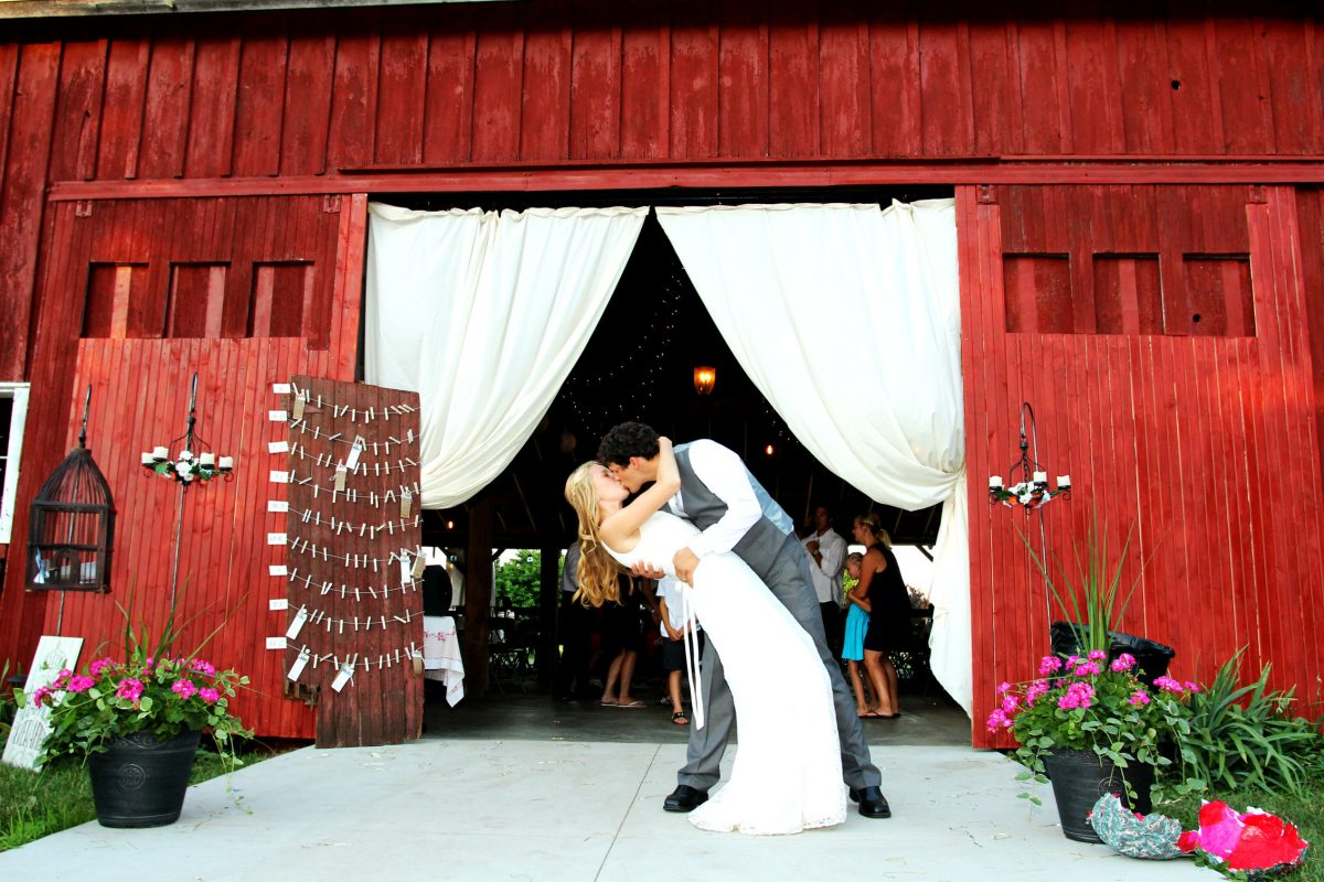 Bride and groom kiss at barn wedding venue Blodgett Wedding Barn in Schoolcraft, Michigan