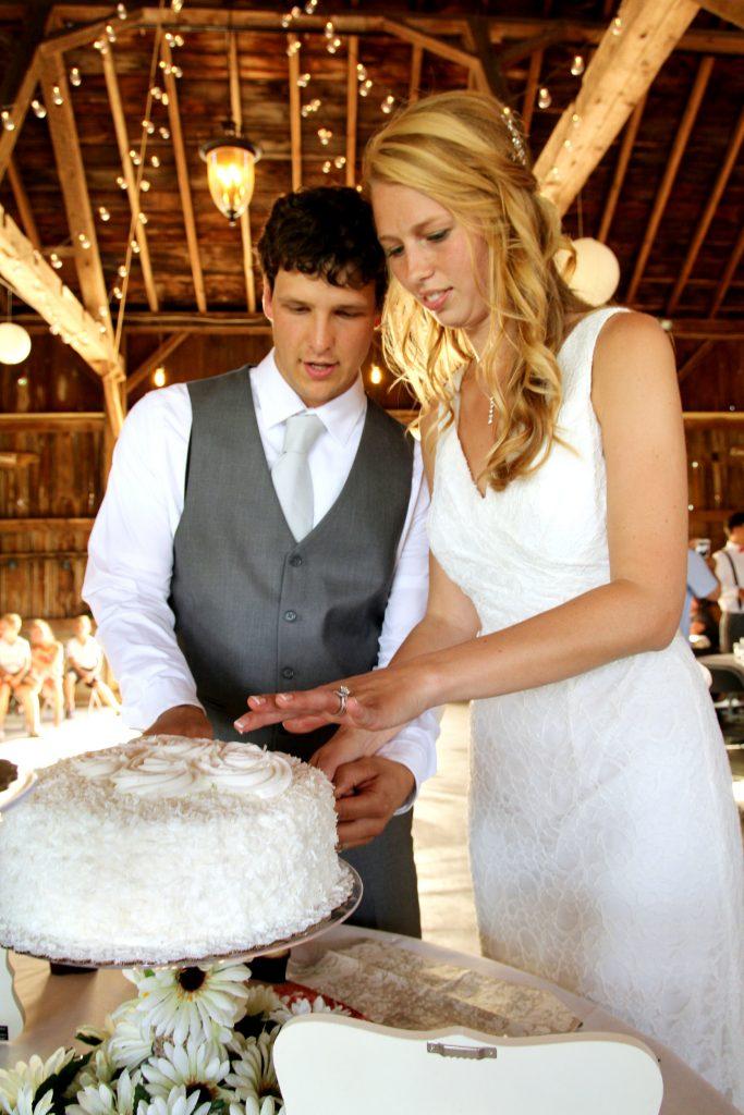 Bride and groom cut wedding cake at barn wedding venue Blodgett Wedding Barn in Schoolcraft, Michigan