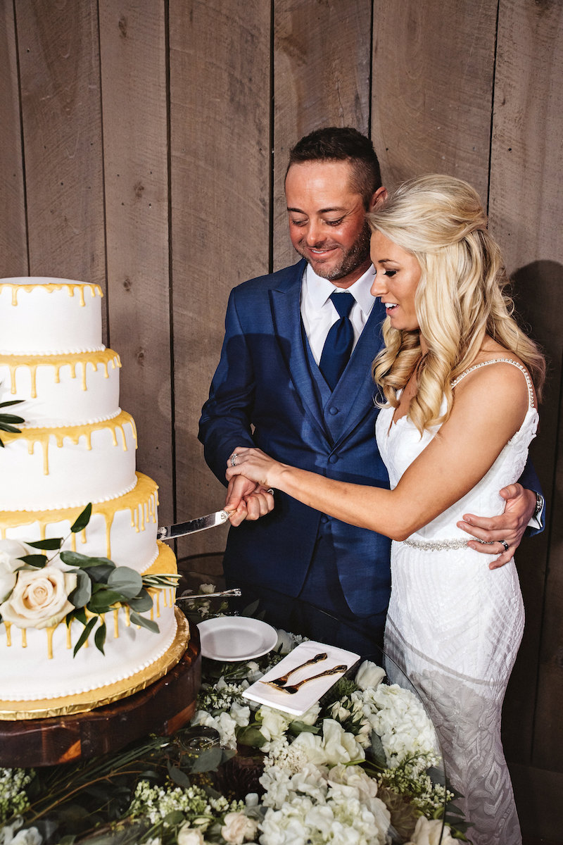 Bride and groom cutting wedding cake at barn wedding at Spring Creek Ranch in Tennessee